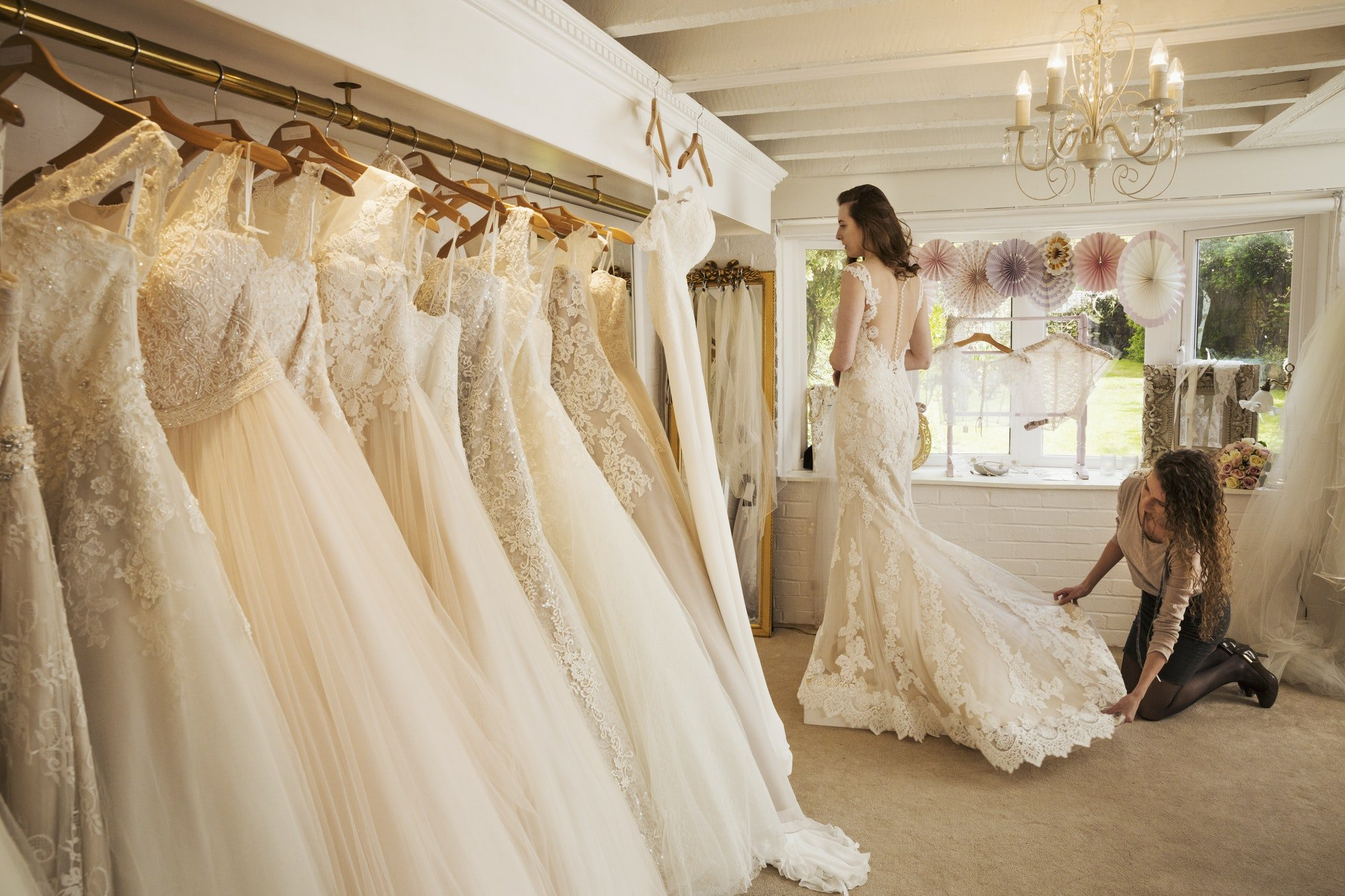 Rows of wedding dresses on display in a specialist wedding dress shop.